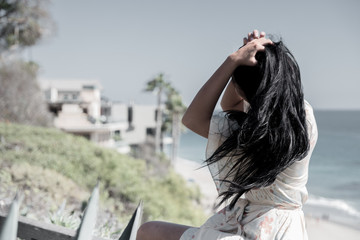Black-haired tan girl playing with her hair in the wind on the cliff above a beach on top of a fence with the background of the shore and a mansion with palm trees. It is breezy.