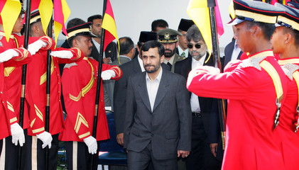 Iranian President Ahmedinejad walks past honour guards after welcoming ceremony in Kuala Lumpur