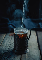 Very hot tea with steam, pouring into a glass in a cup holder on a wooden vintage rustic table. Black background. Dark and moody. Close up, selective focus