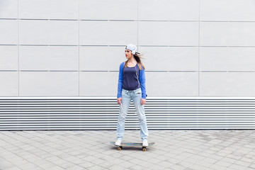Young girl driving skateboard in urban environment.