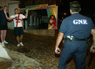 ENGLAND SOCCER FAN RAISES HIS ARMS IN FRONT OF PORTUGUESE POLICEMAN IN ALBUFEIRA.