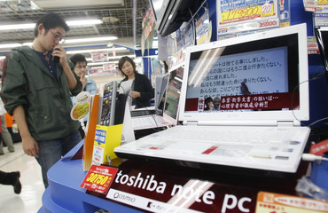 A man looks at laptop computers at an electronics retailer in Tokyo