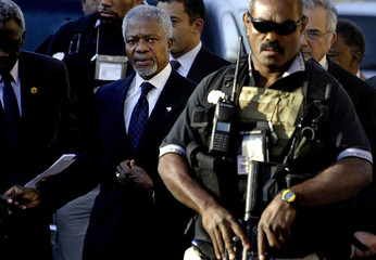 UN Secretary-General Annan is escorted by bodyguards to a news conference in Baghdad