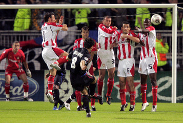 Juninho of Lyon scores from a free kick during a Champions League Group F match against Olympiakos at Gerland stadium in Lyon