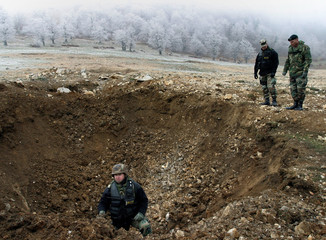 U.S. SOLDIERS EXAMINE CRATER AFTER WEAPONS DESTROYED IN BOSNIA.