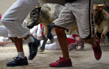 Bulls and steers jump over runner during second running of bulls at San Fermin festival in Pamplona.