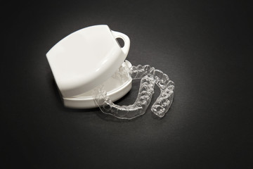 Isolated transparent teeth prosthesis with its box over black for design