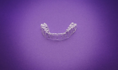 Isolated transparent teeth prosthesis over purple for design
