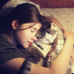 teenage girl hug cuddle cat in bed with book and lamp