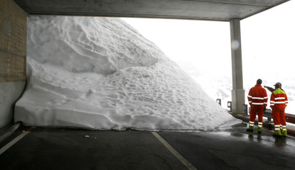 Workers stand in front of the snow covered Saint Gotthard mountain pass road in the Swiss Alps