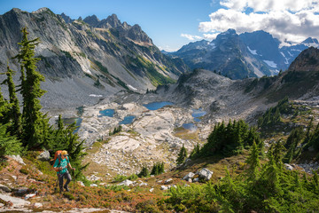 Man hiking by mountains in sunshine, Alpine Lakes, Washington, USA