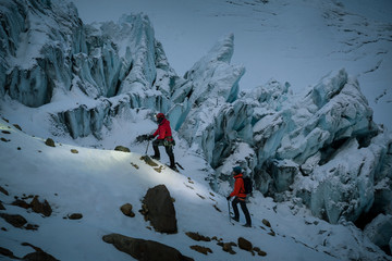 Two people ascending snow covered hillside by rock peaks, Ecuador, South America