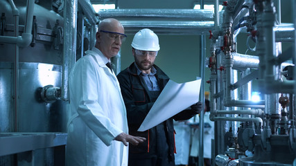 The doctor and the engineer looking at the blueprint in the factory. Horizontal indoors shot.