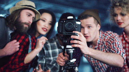 Group of young diverse people filmmakers gathered behind DSLR camera on tripod to check the angle of shooting in studio. Pointing fingers and smiling