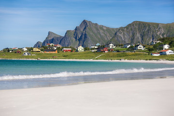 View from beach overlooking the sea, village and mountain landscape, Norway