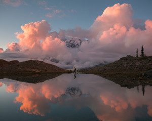Reflection onto lake of Mount Rainier, clouds and person at Mount Rainier National Park, Washington State