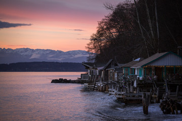 Wooden houses over water at sunset, snowcapped mountains in background