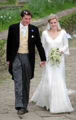 Britain's Laura Parker Bowles (R) and her husband Harry Lopes (L) leave following their wedding at S..