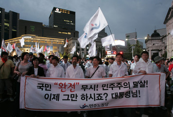 Protesters take part in a street rally demanding the renegotiation of the U.S. beef import deals and the resignation of its President Lee in Seoul