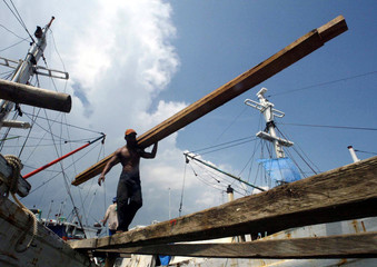 Indonesian workers unload certified timber at the port of Gresik in East Java province