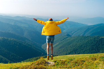 Man in yellow raincoat, jeans shorts standing at top of Carpathian mountains with view of peaks at horizon. Landscape. Nature. Valley. Travel. Freedom. Vacation. Hills. Success. Contemplation. Flight