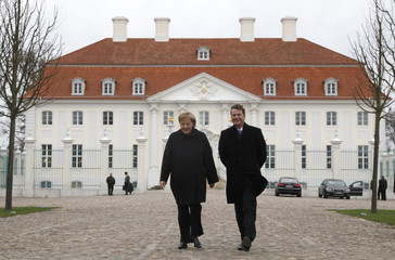 German Chancellor Merkel and Foreign Minister Westerwelle leave government guest house Schloss Meseberg