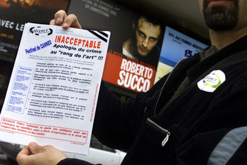 Plainclothes policemen hand out leaflets outside a cinema in protest against a French movie depictin..