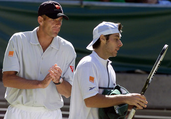 French team captain Guy Forget (L) encourages his top singles player Sebastien Grosjean during his m..