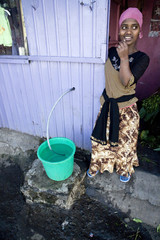 An Ethiopian girl fills a bucket  with water in a village in Addis Ababa