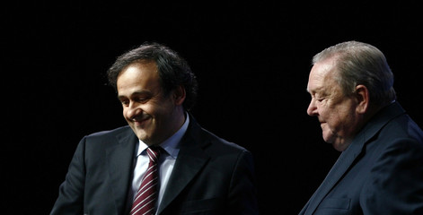 Frenchman Platini smiles next to outgoing UEFA president Johansson after Platini was elected the new president in Duesseldorf