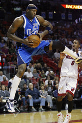 Dallas Mavericks Erick Dampier grabs a rebound away from Miami Heat's Mario Chalmers during first quarter NBA basketball action in Miami