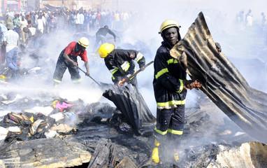 Firefighters salvage burnt property at St. Balikuddembe market in Kampala Uganda