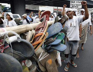 Farmers clench their fists while carrying worn-out sandals worn during their 1700-km journey from Sumilao to Manila