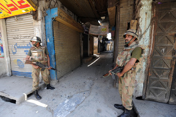 Pakistani soldiers stand on guard in a market in Mingora, the main town in Swat valley
