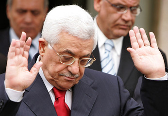 Palestinian President Mahmoud Abbas gestures as he leaves the guest palace in Amman