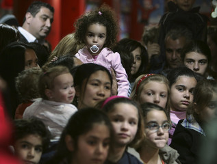 Children watch a man dressed as Santa Claus during a Christmas promotional event  in Amman