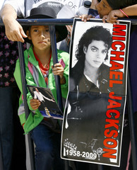 A child stands next to a picture of Michael Jackson in Mexico City