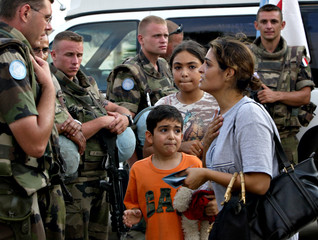 A mother shows U.S. passports to a French U.N. officer after hearing that evacuation by United Natio..