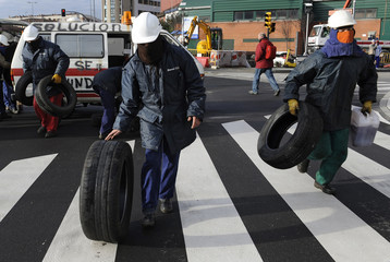 Shipyard workers carry tyres to make a barricade during a protest in Gijon