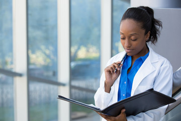 Closeup portrait of friendly, thinking confident female doctor, healthcare professional with labcoat, holding pen to face and holding notebook pad. Isolated hospital clinic background.