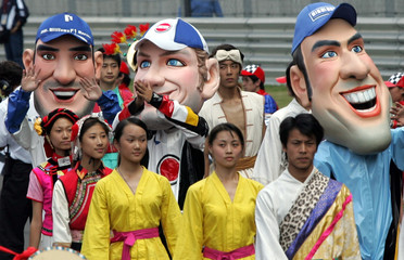 Wearing masks representing F-1 drivers, Chinese performers march during the openning ceremony of ...