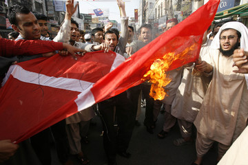 Traders burn a Danish flag during a protest against the reprinting of cartoons depicting Prophet Mohammad in Danish newspapers, in Lahore