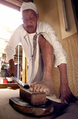 AN EGYPTIAN LEG IRONER IRONS IN HIS SHOP IN CAIRO.