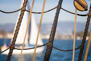 Nautical background. Close up of sailboat ropes, cables and wood pulley in grid pattern. Blurred white sailboat and blue water in the background.