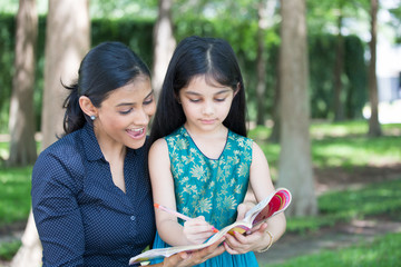 Closeup portrait, young family enjoying coloring book, drawing, isolated outdoors outside background