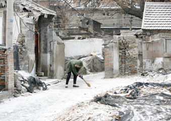 A woman clears snow in front of her house in Beijing