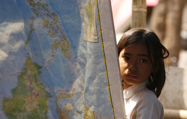 A student of Sekolah Darurat Kartini stands behind a map of Indonesia at their new makeshift classroom after the government evicted them from their old location in Jakarta