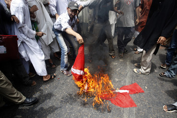 Protesters burn a Danish flag during a protest against a Dutch film and the reprinting of cartoons of Prophet Mohammad in Danish newspapers, in Karachi
