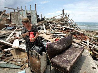 Xiomara Santa Maria holds onto a thermous she found underneath the remains of her house in the wake ..
