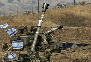 Israeli soldiers stand near mobile artillery units by the Israel-Lebanon border